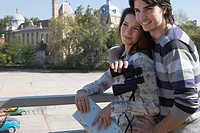 Couple holding binoculars and a map outdoors smiling