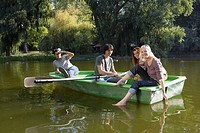 Four friends in a rowboat smiling