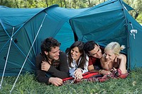 Four people lying in a tent at campsite smiling