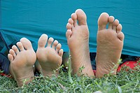 Two people's feet sticking out of tent door