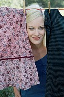 Woman peeking through laundry hanging on clothesline smiling