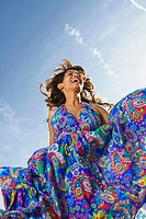 Woman outdoors laughing in a colorful dress
