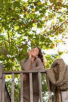 Woman with eyes closed leans on railing outside
