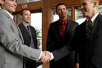 Business men shaking hands in hotel foyer
