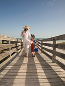 Mother and son 4-5 walking back from beach along wooden boardwalk