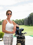 Woman leaning on golf bag, standing on drive range, portrait