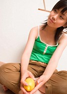 Young woman sitting on floor with lemon