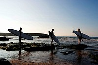 Three people holding surfboards standing on large rocks