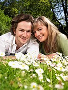 Couple lying in the grass smiling