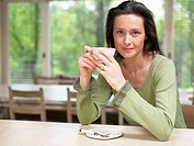Woman holding a mug at a table indoors smiling