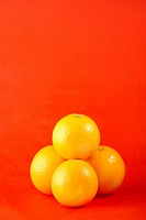 An arrangement of oranges against red background