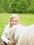 Young girl smiling and crouching by a sheep in a field