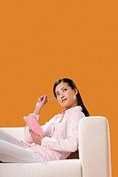 Businesswoman with pen and organizer looking up thinking