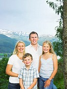 Family outdoors by tall tree smiling