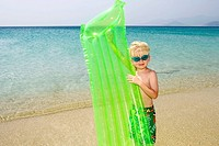 Young boy at the beach with an inflatable raft