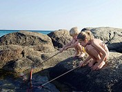 Young boy and young girl crouched on rocks fishing with nets