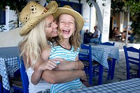 Woman with young girl at an outdoor restaurant smiling