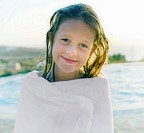 Young girl wrapped in towel by pool smiling