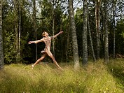 Woman jumping in a forest smiling