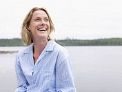 Woman laughing outdoors by the water