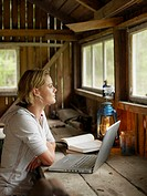 Woman with laptop and book sitting at table in cabin