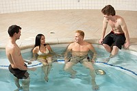 Four people relaxing in swimming pool