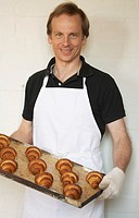 Portrait of mid adult man wearing apron, holding baking sheet with croissants