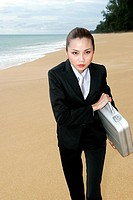 Businesswoman holding briefcase on the beach