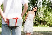 Man hiding a surprise gift from his girlfriend