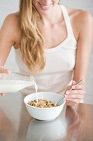 A woman pouring milk onto cereal