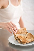 A woman holding a slice of toast