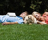 Couple lying on grass with dog