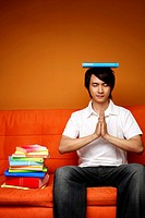 Man balancing a book on his head