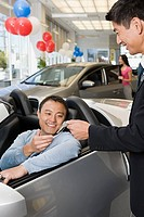 Man and salesman at car dealership