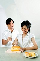 Woman cutting bread, man holding a glass of milk