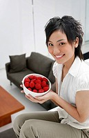 Woman holding a bowl of strawberries