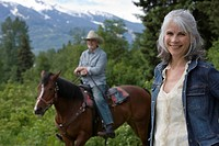 Portrait of mature couple on alpine meadow, woman in foreground smiling, man on horse in background