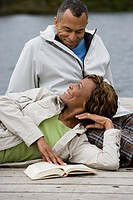 Mature couple relaxing on pier, looking in eyes, smiling