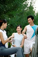 Man and women in sportswear chatting in the park