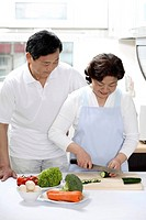Senior man and woman preparing food in the kitchen