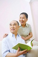 Senior man and woman looking away while reading book