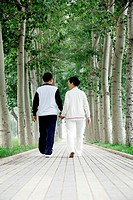 Senior man and woman holding hands while walking in the park