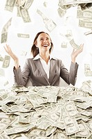 Businesswoman surrounded by large pile of money
