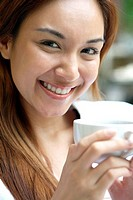 Woman holding a cup smiling at the camera