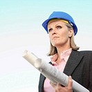 Female building surveyor holding blueprints, outdoors