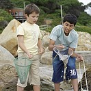 Two boys 10-12 playing with nets on beach
