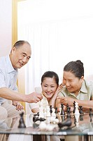 Woman playing chess game with senior man and woman