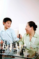 Senior woman and boy playing chess game