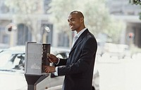 Business man paying parking meter in street