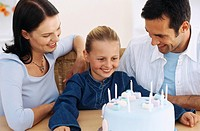 Parents with daughter 10-11 sitting at table with birthday cake